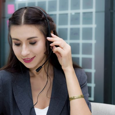 Attractive smiling caucasian woman call center with microphone headset offering customer service waiting to answer various problems about the product use and good after-sales service.