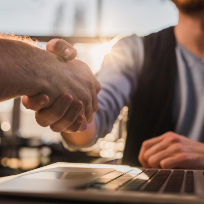 Close up of two men making a deal and shaking hands.