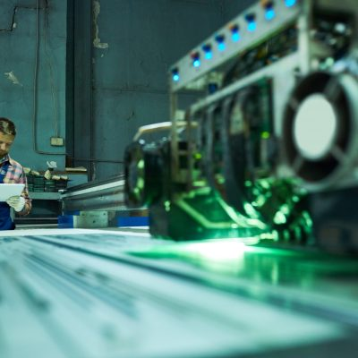 Portrait of young factory worker operating modern laser engraving equipment in industrial workshop, copy space